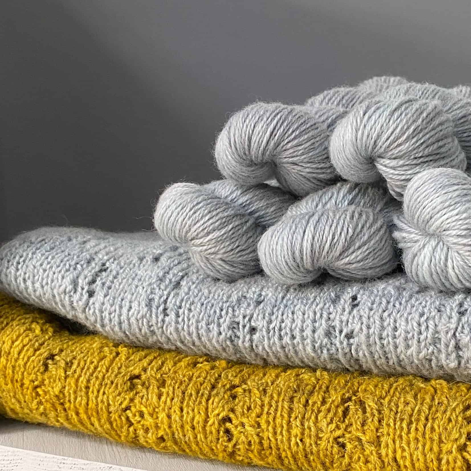Gray yarn piled on gray and gold handknits.