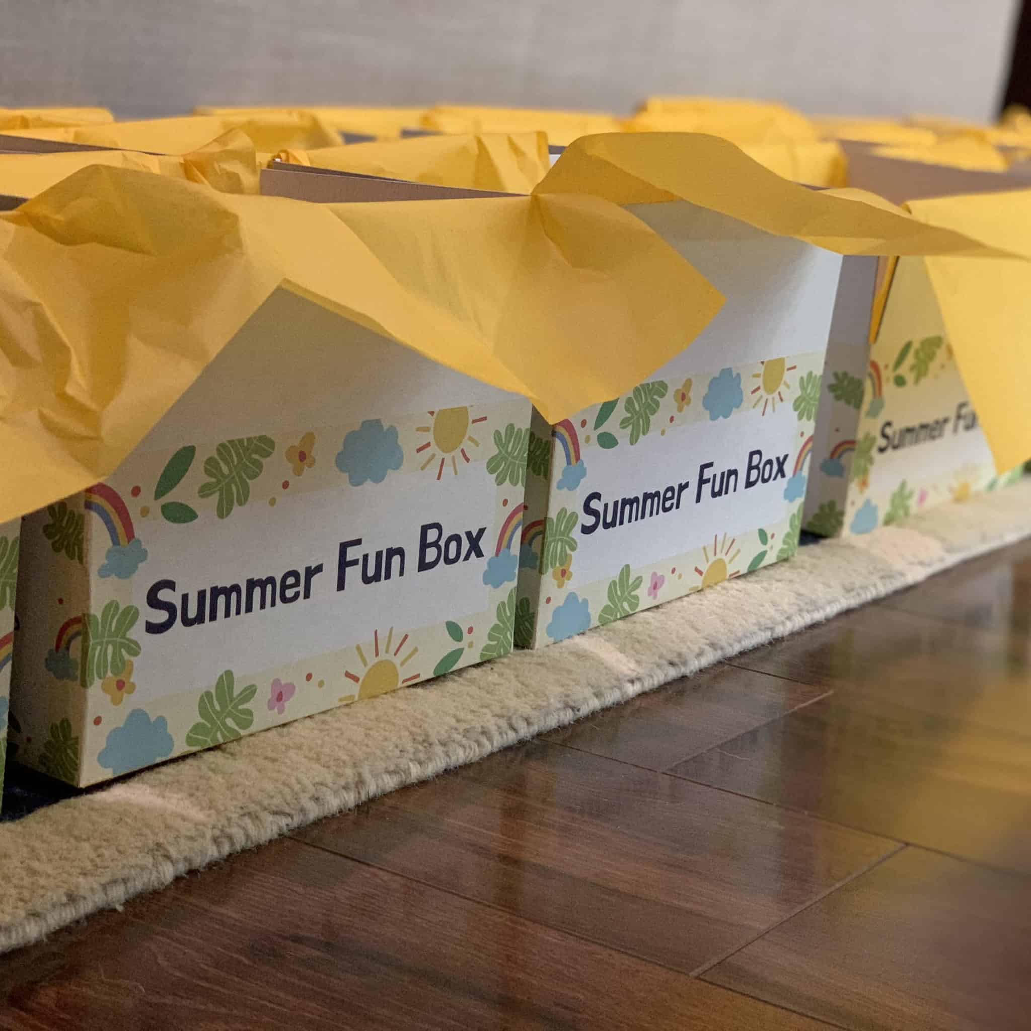 Boxes with yellow tissue paper labeled summer fun box.