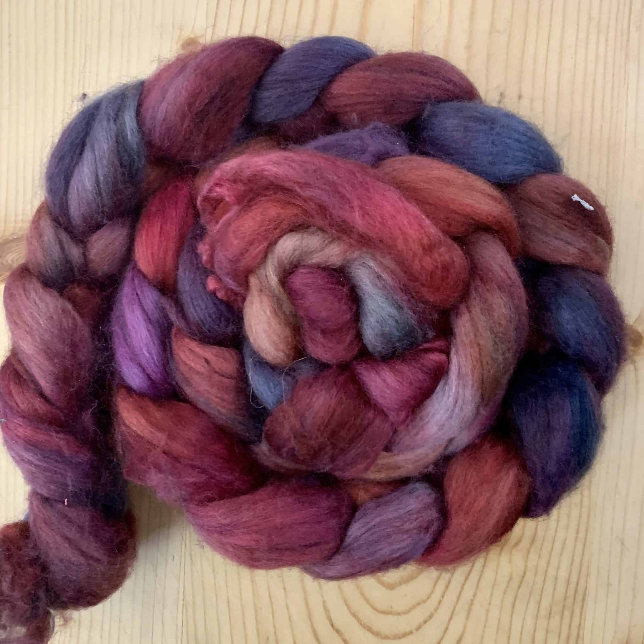 A coiled braid of pink and purple fiber.