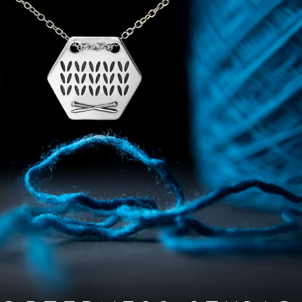 A silver honeycomb necklace with knit stitches next to a cake of blue yarn.