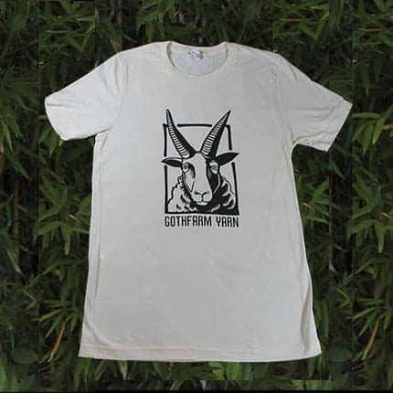 A white t-shirt with a horned sheep that reads Gothfarm Yarn.