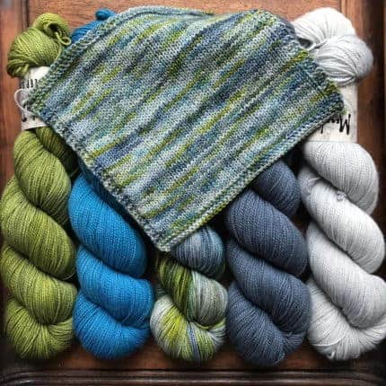 A blue, green and gray knitting swatch over skeins of yarn.