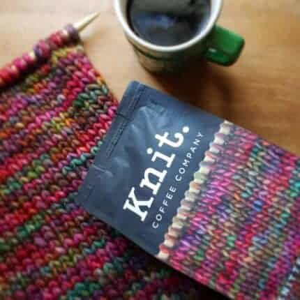 A black bag with the words Knit. coffee company next to a green mug of coffee and a red, green and pink knitting on a needle.