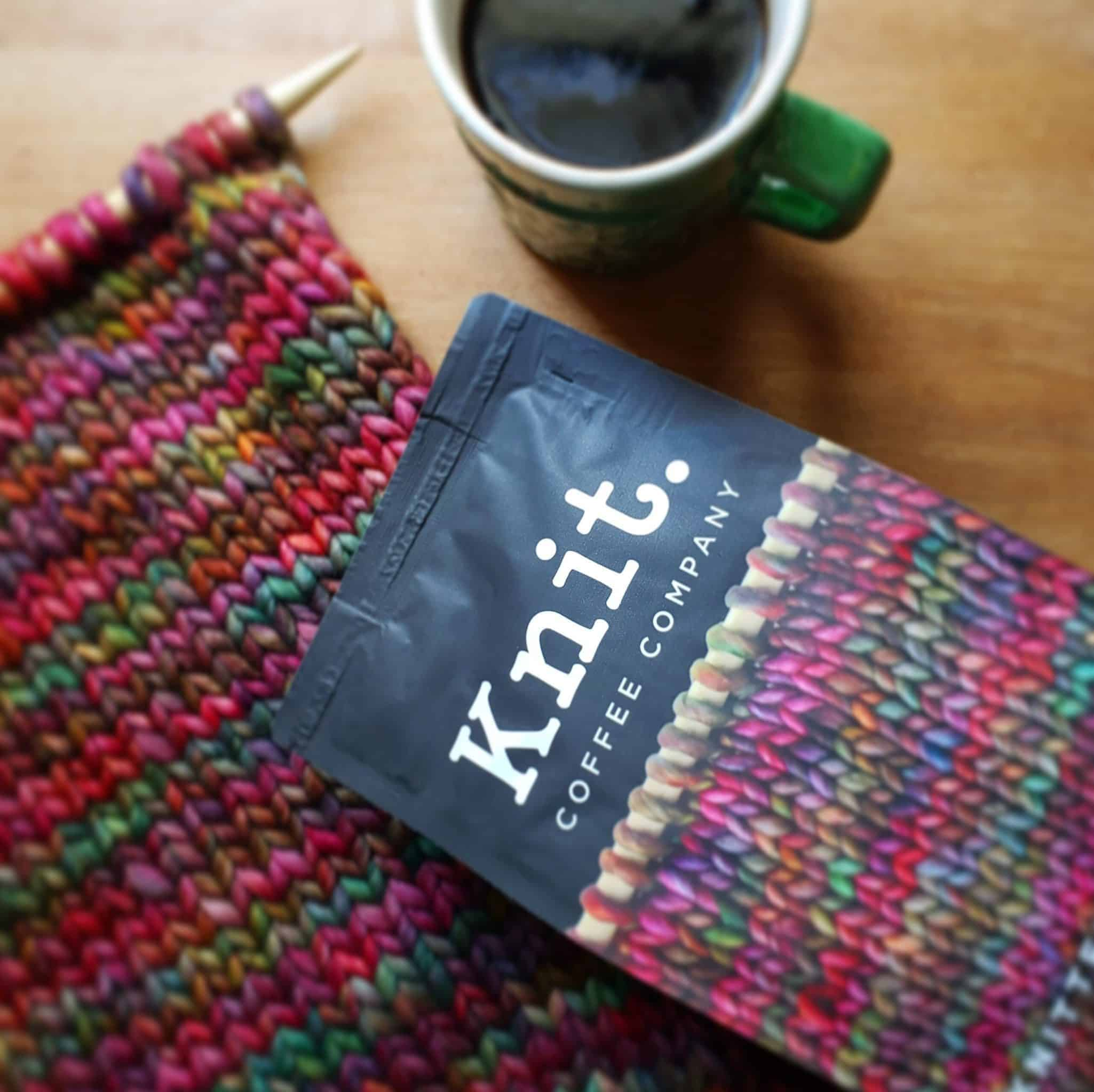 A black bag with the word Knit next to a cup of coffee and a red, green and pink knitting on a needle.