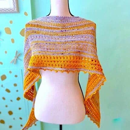 A yellow and lilac shawl on a dress form.