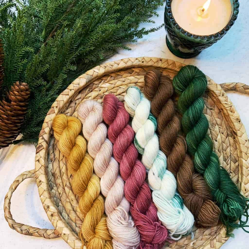 Gold, pink, red, white, brown and green yarn in a flat basket.