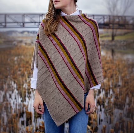 A beige poncho with pink and purple stripes.