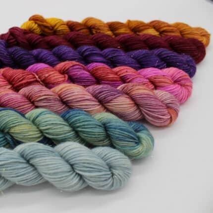 Mini skeins of blue, green, pink, purple and orange yarn.