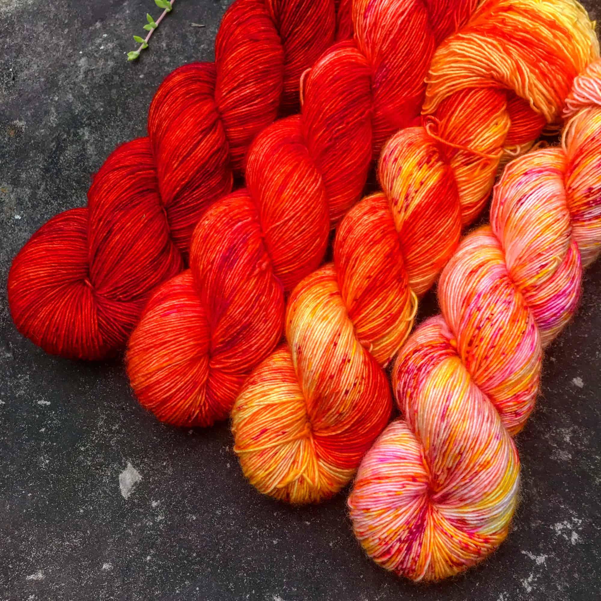 A four-skein fade set of red-orange yarn.