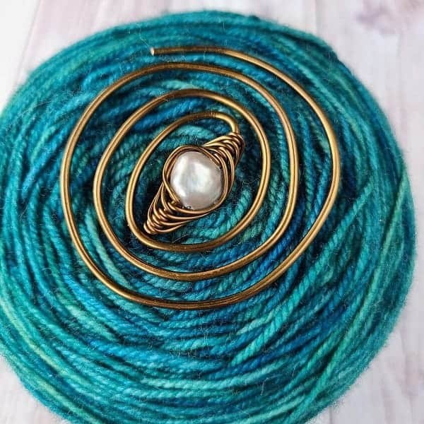 A copper swirl with a pearl on a cake of turquoise yarn.