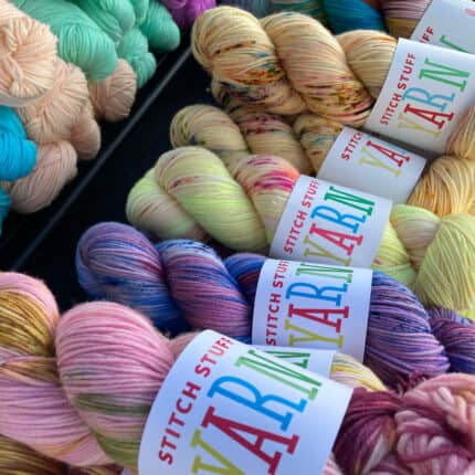 Skeins of pink, purple and yellow speckled yarn.