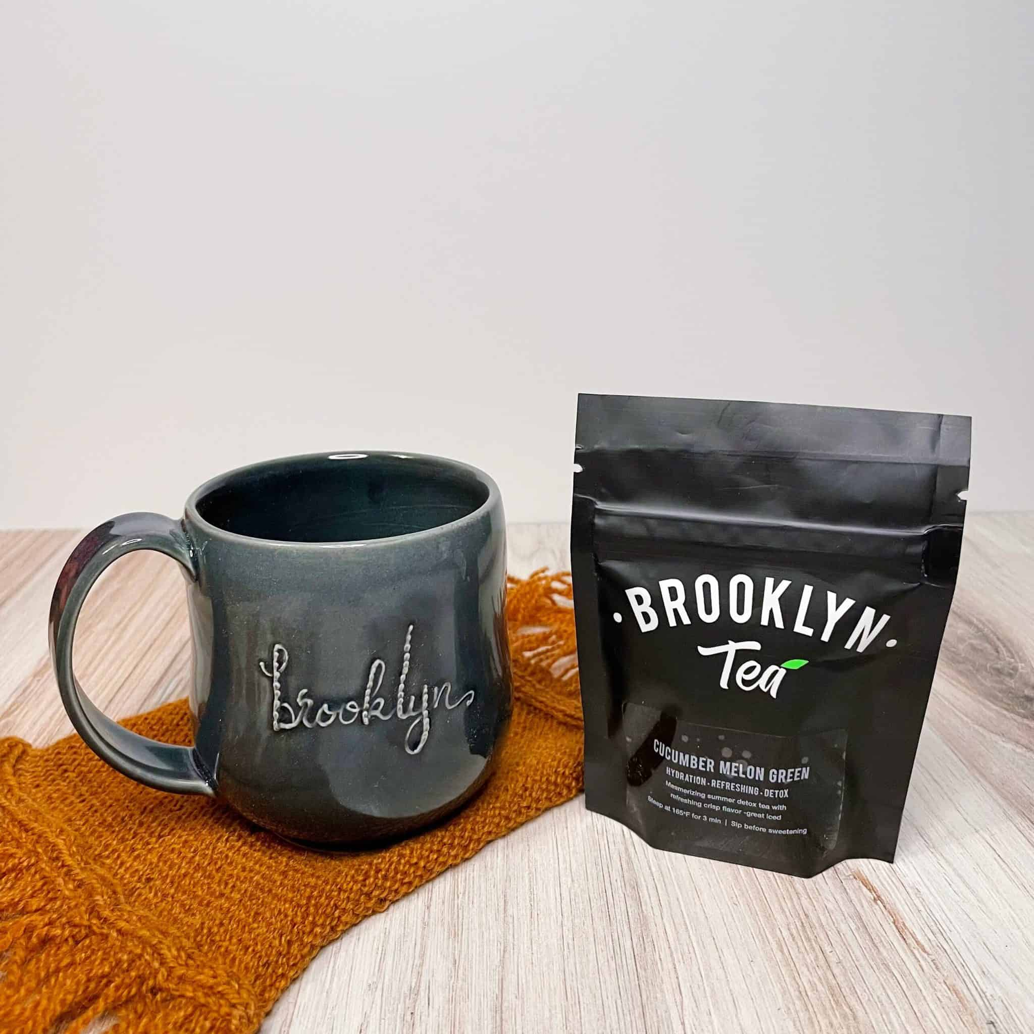 A gray mug with Brooklyn in script sits on an orange swatch of knitting next to a black pouch of Brooklyn Tea.