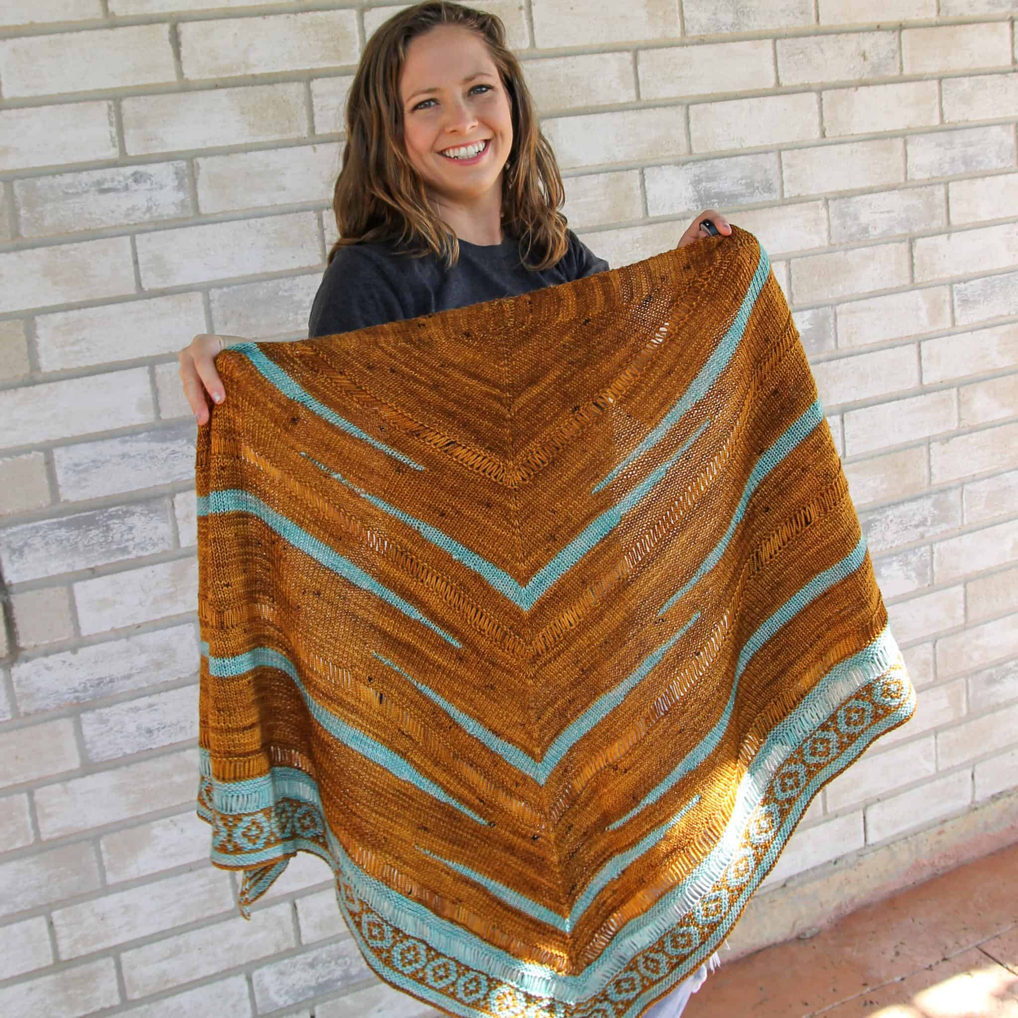 A woman holds up a gold and turquoise triangular shawl.
