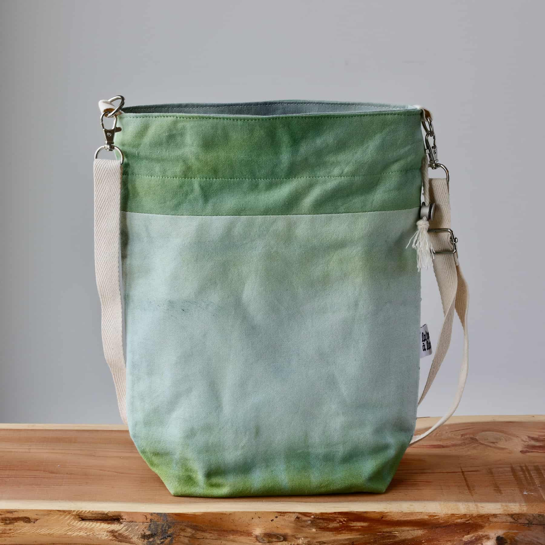 A light green canvas bag with a beige leather strap sits atop a wooden table.