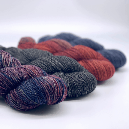 Skeins of purple, gray, red and blue yarn.