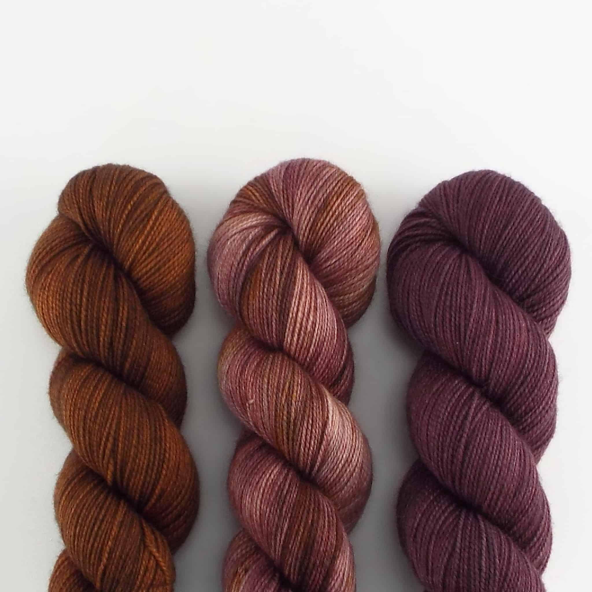 Three skeins of plum yarn.