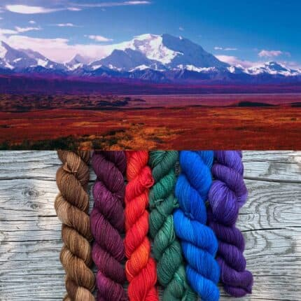 A snow-covered mountain and skeins of brown, plum, red, green, blue and purple yarn.