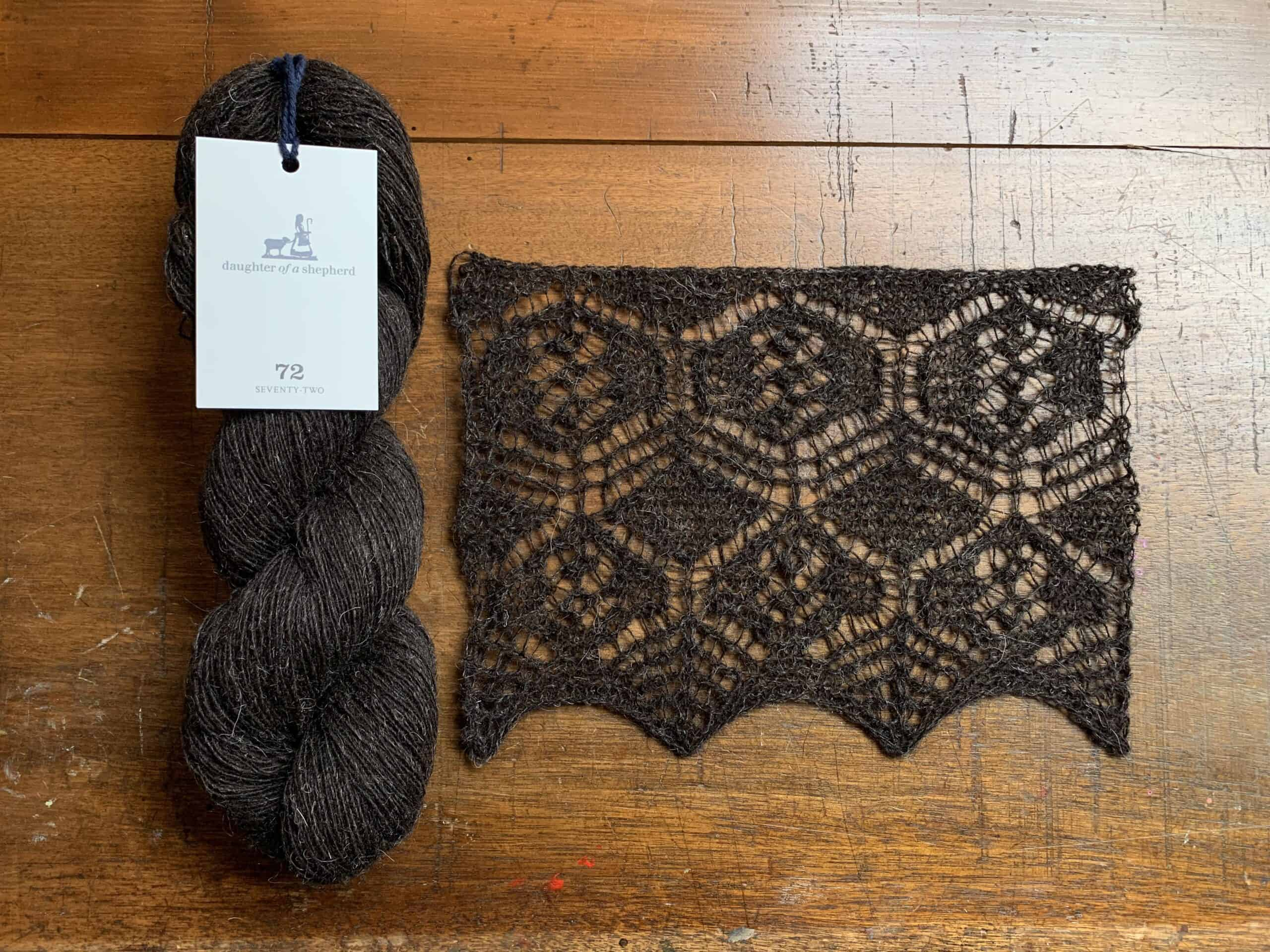 A skein of dark brown yarn and a piece of lace knitting.