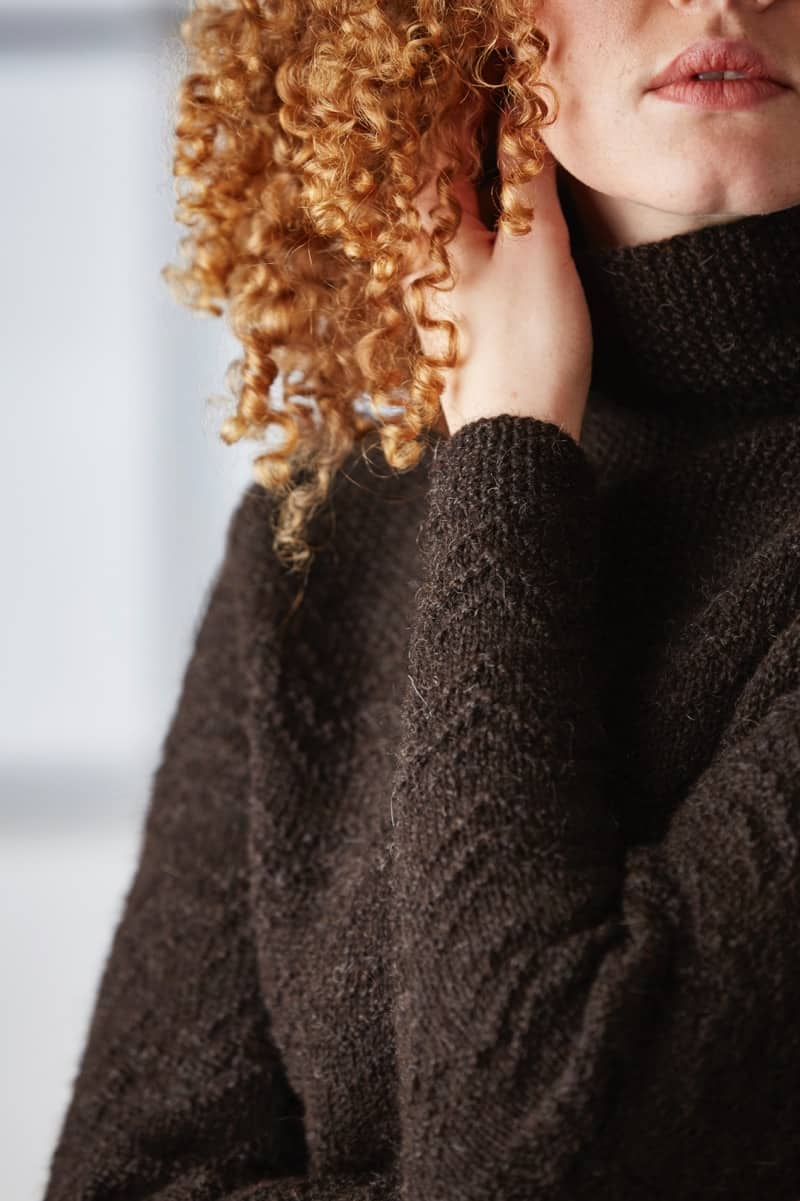 The sleeve and body of a dark brown textured sweater.