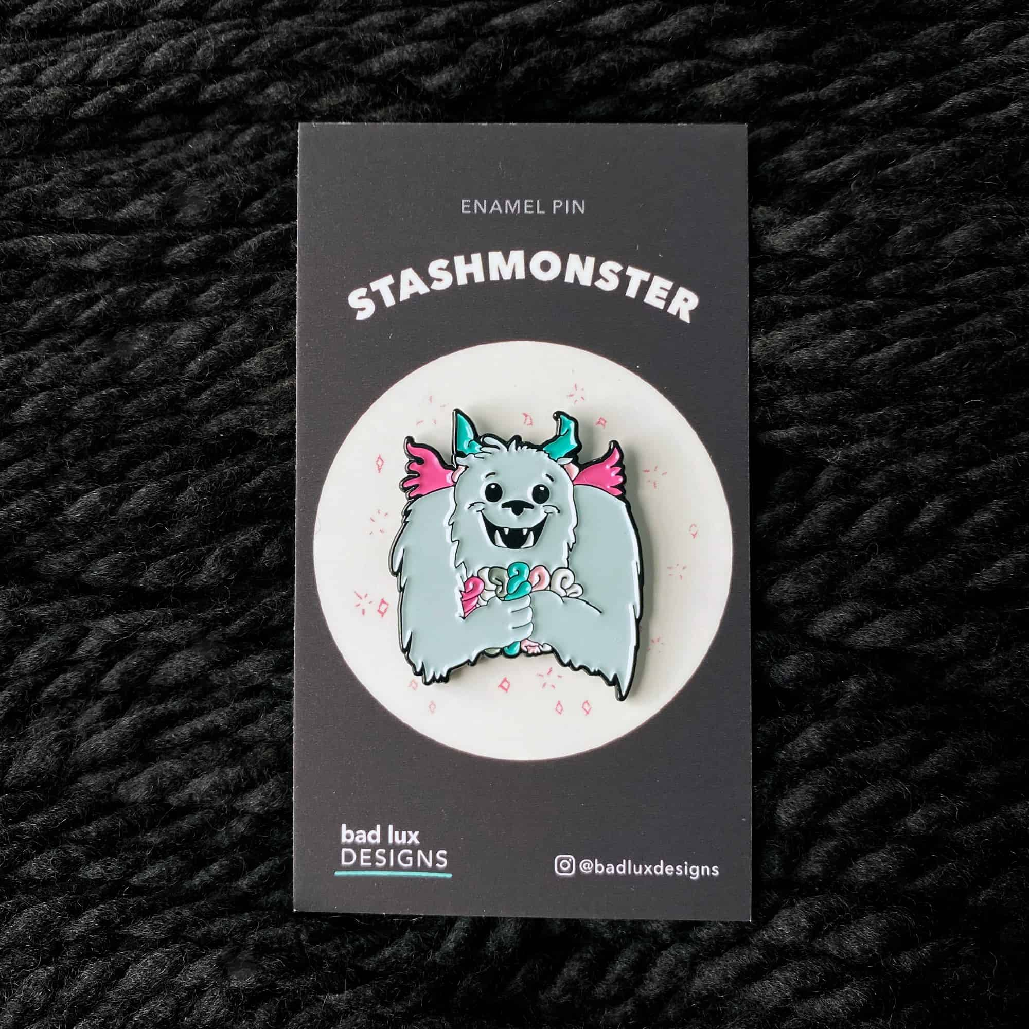 An enamel pin with a blue monster clutching skeins of pink and teal yarn.