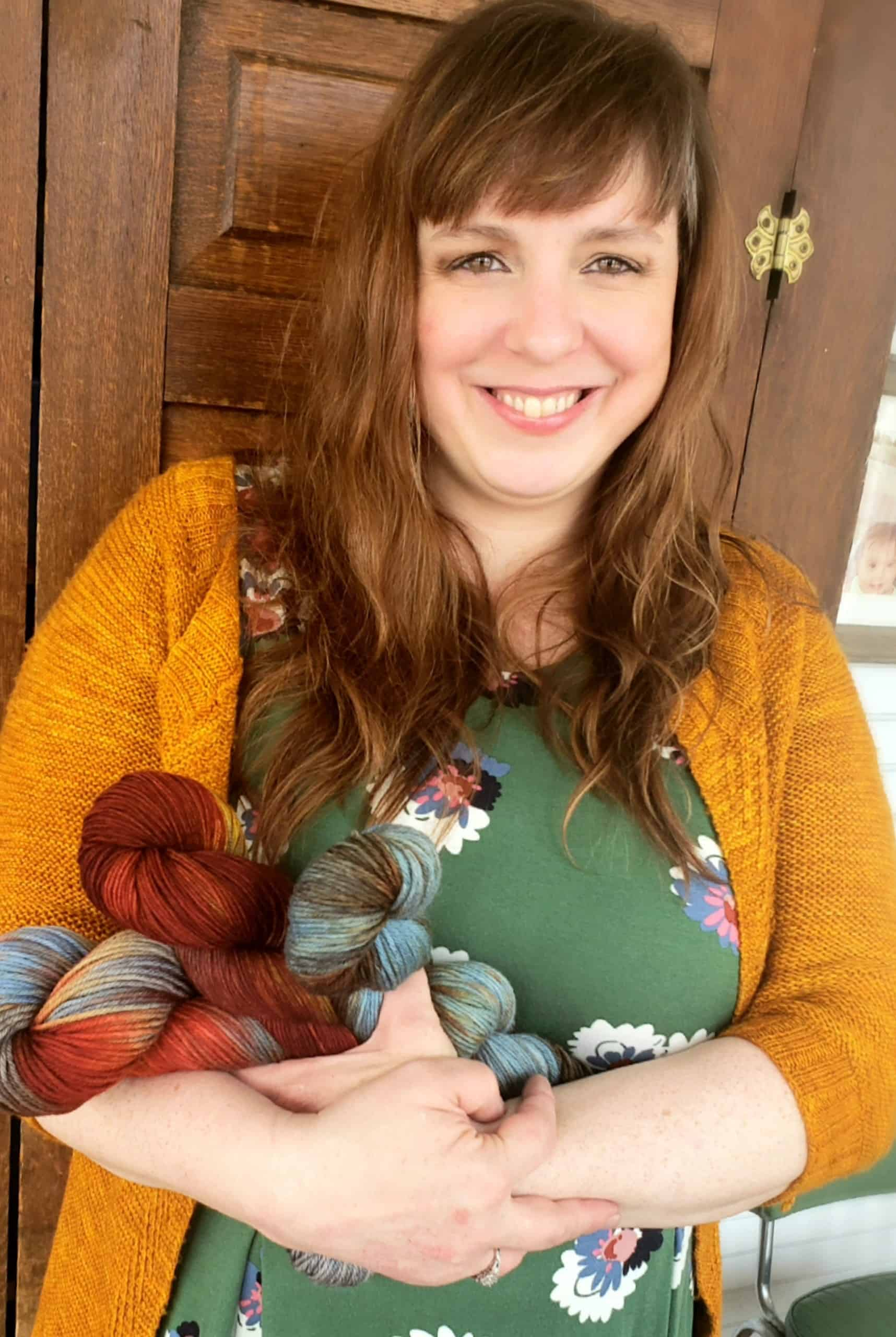 A light-skinned woman with light brown hair wearing a gold sweater holding yarn.