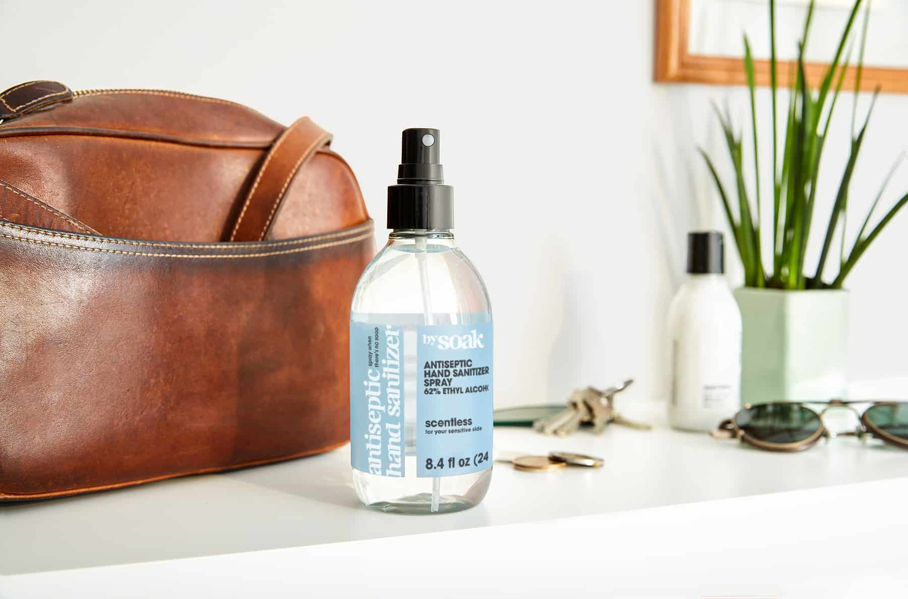 A spray bottle with a blue label next to a brown leather bag.