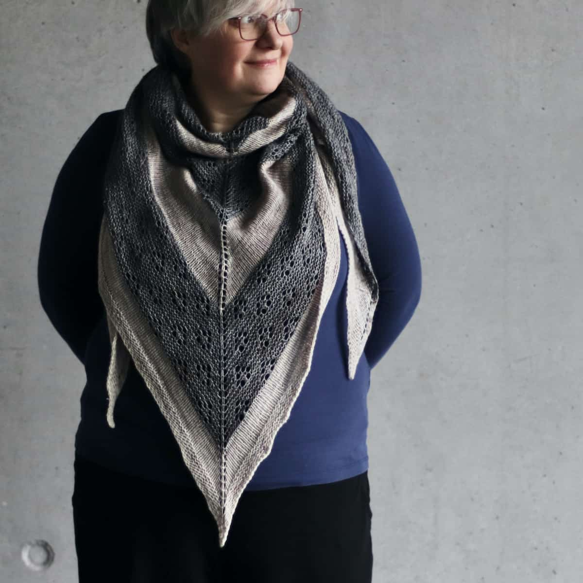 A light-skinned woman with gray hair wears a large gray striped triangle shawl bandana-style.