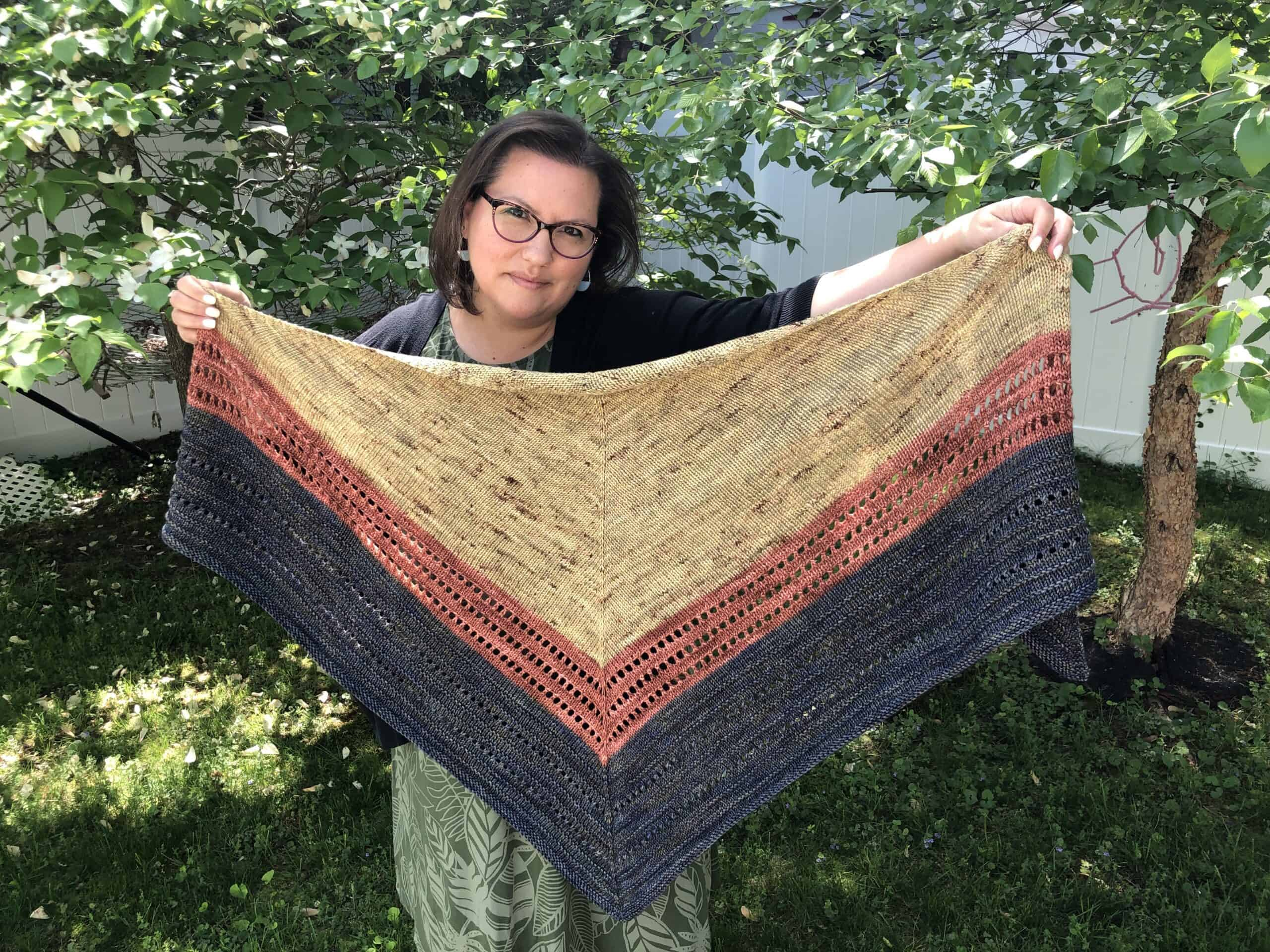 A woman holds up a beige, rust and gray triangle shawl.