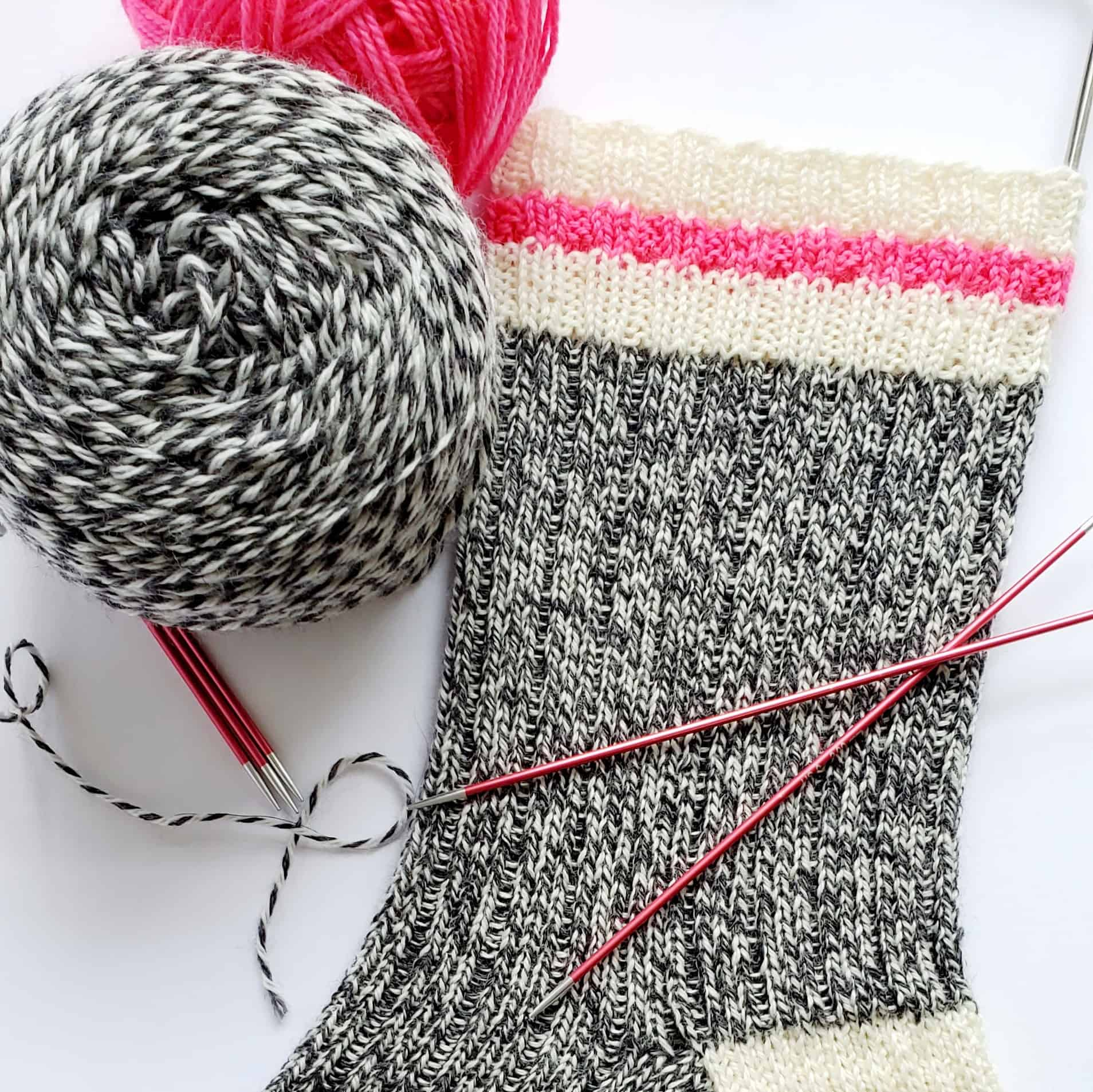 A sock knit with black and white marled yarn with a pink stripe at the top.