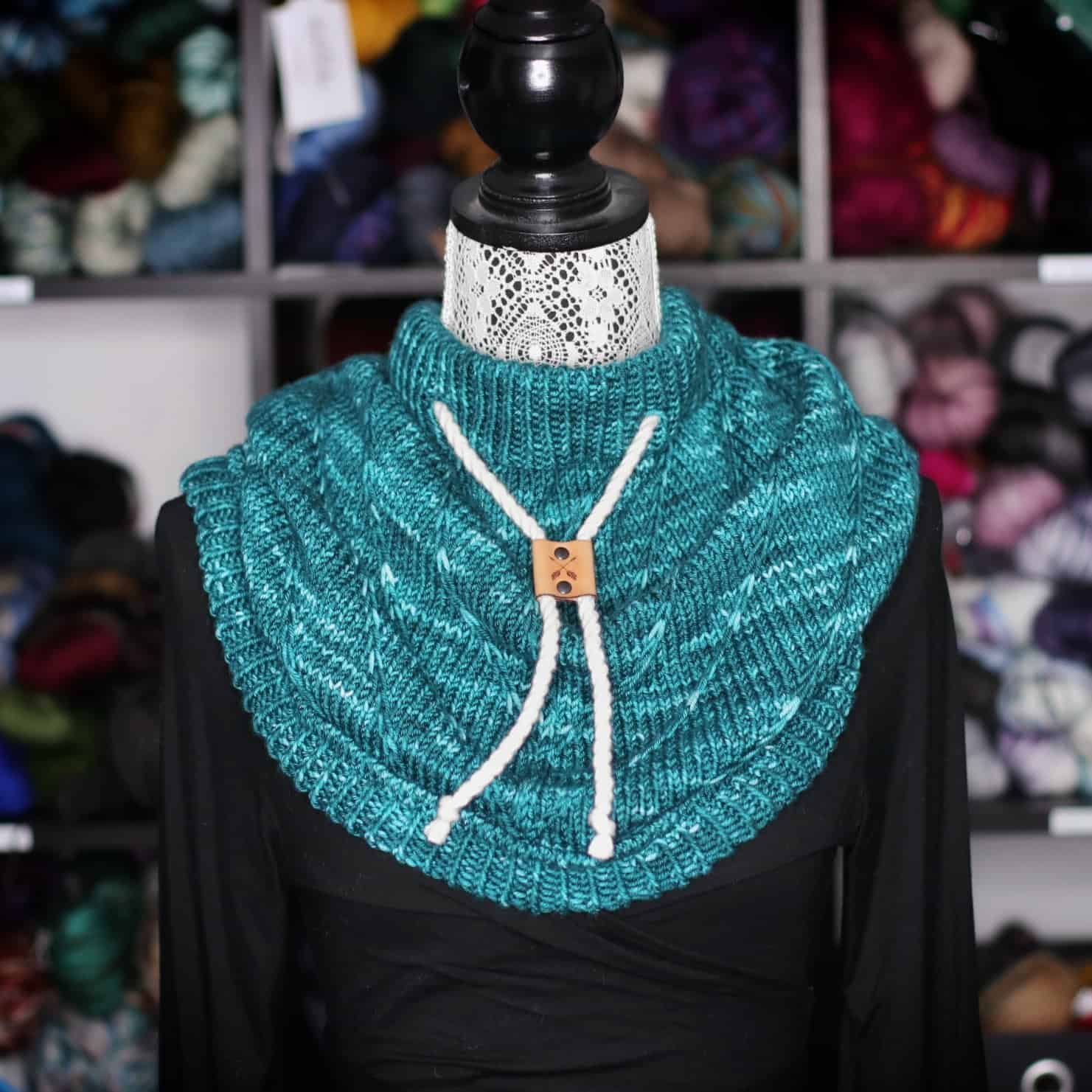 A teal cowl with a white cord on a dress form.