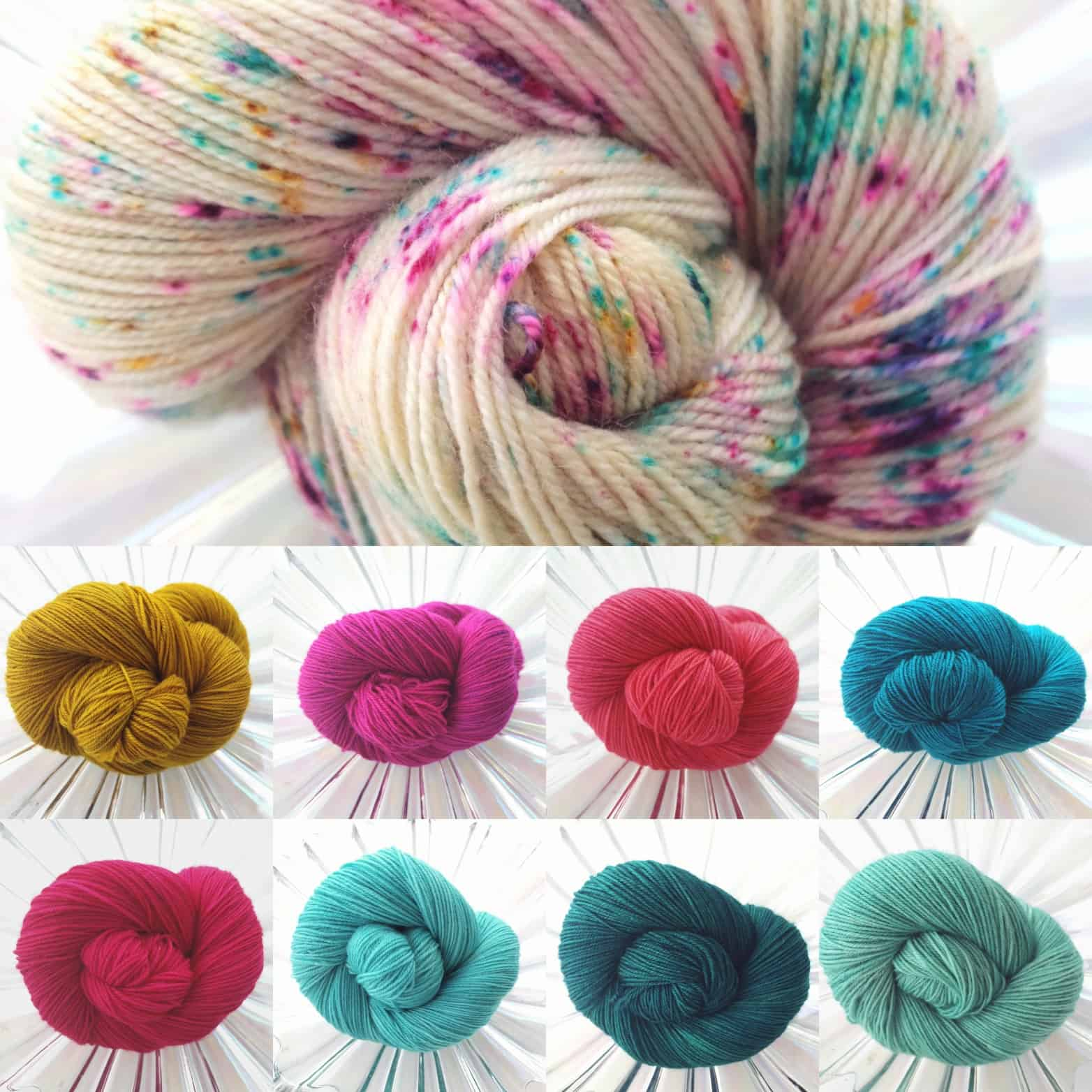 A white yarn speckled with gold, pink, teal and aqua and corresponding coiled skeins of yarn.