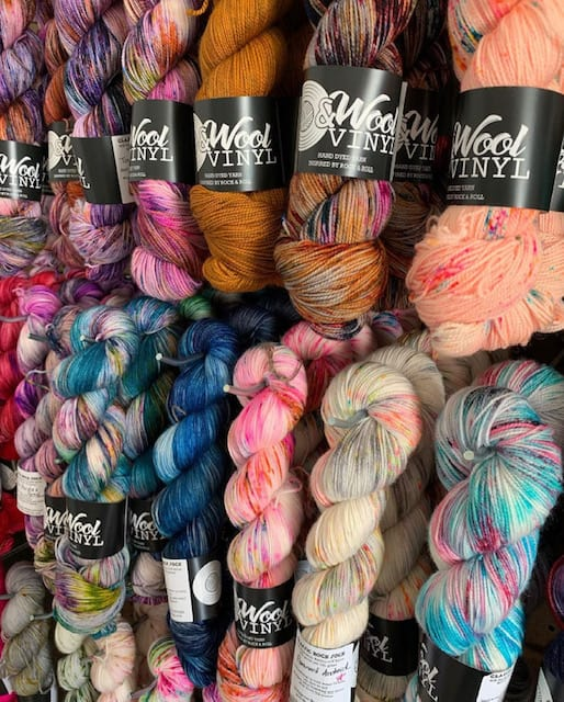 A wall of colorful yarn with black labels.