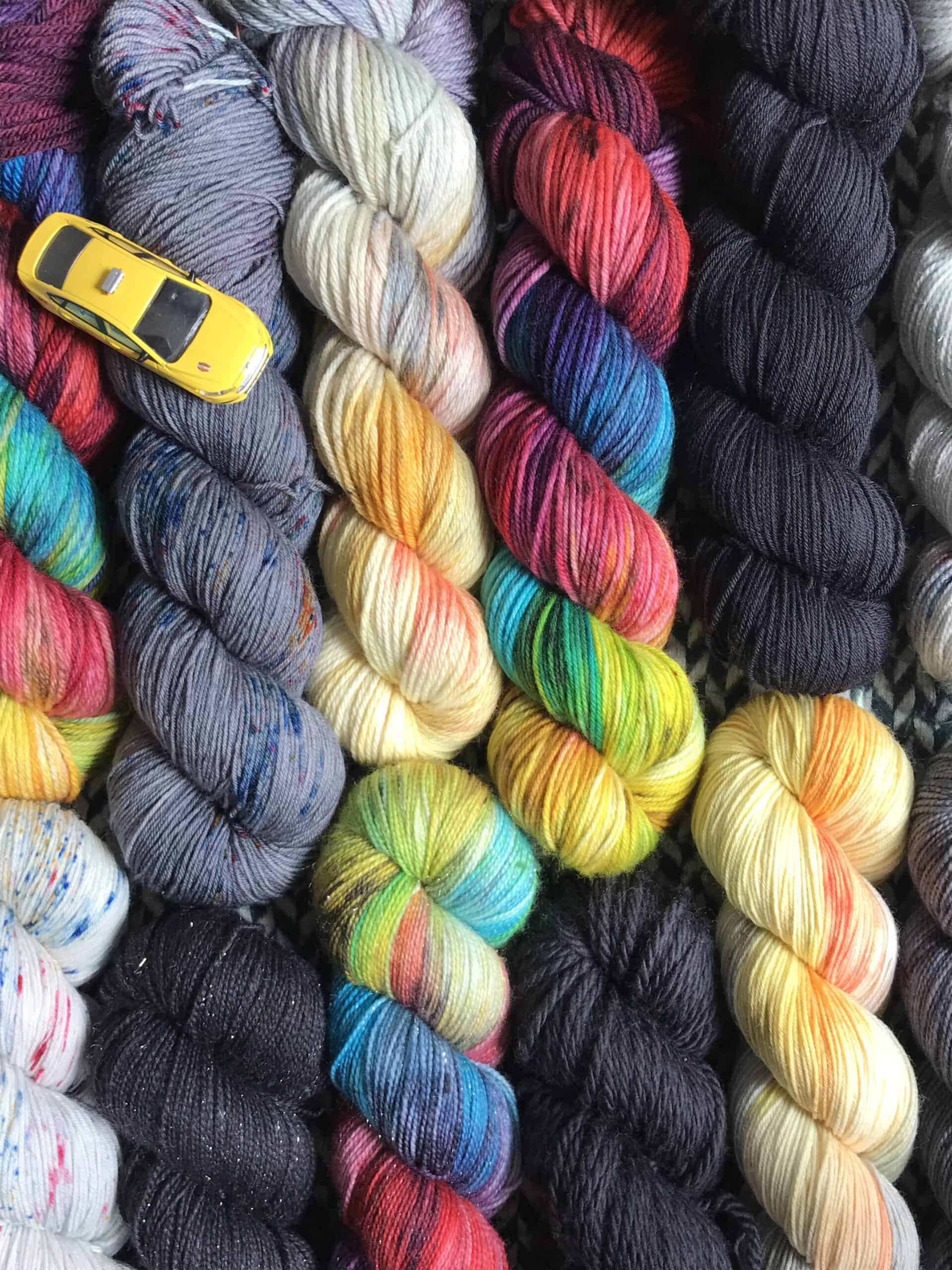 Skeins of colorful yarn and a small yellow taxi.