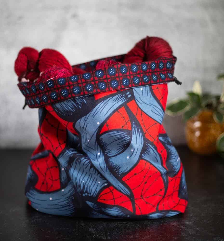 Red yarn peeking out of a blue and red floral drawstring bag.