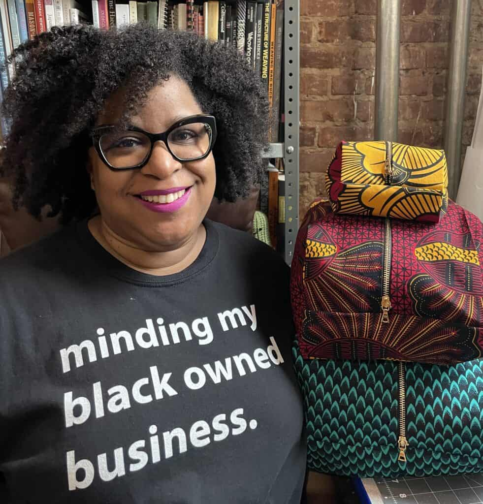 A black woman wears a T-shirt that reads minding my black owned business.