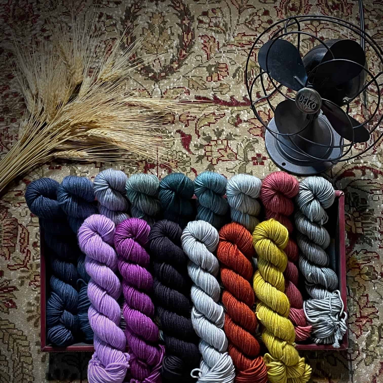 Small skeins of colorful yarn in two rows next to a black fan.
