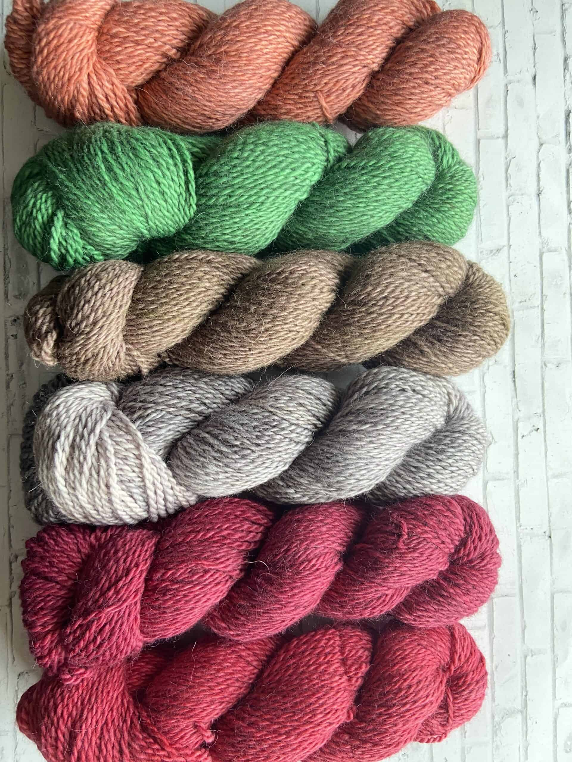 Skeins of green, beige, gray and pink yarn.
