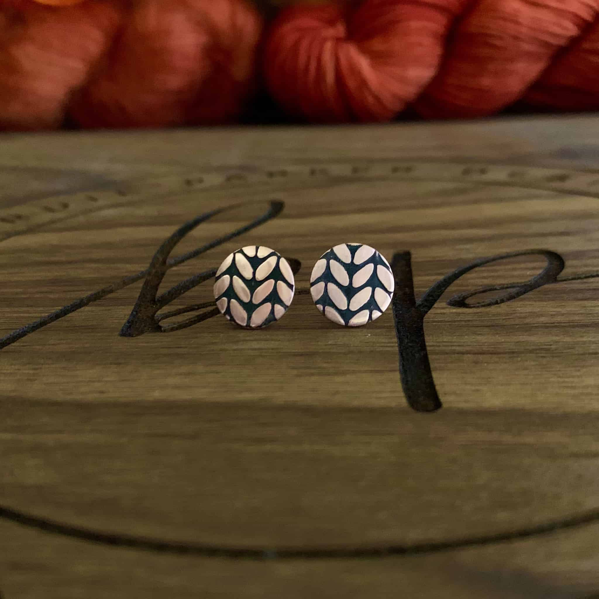Round earrings with etched knitting stitches.