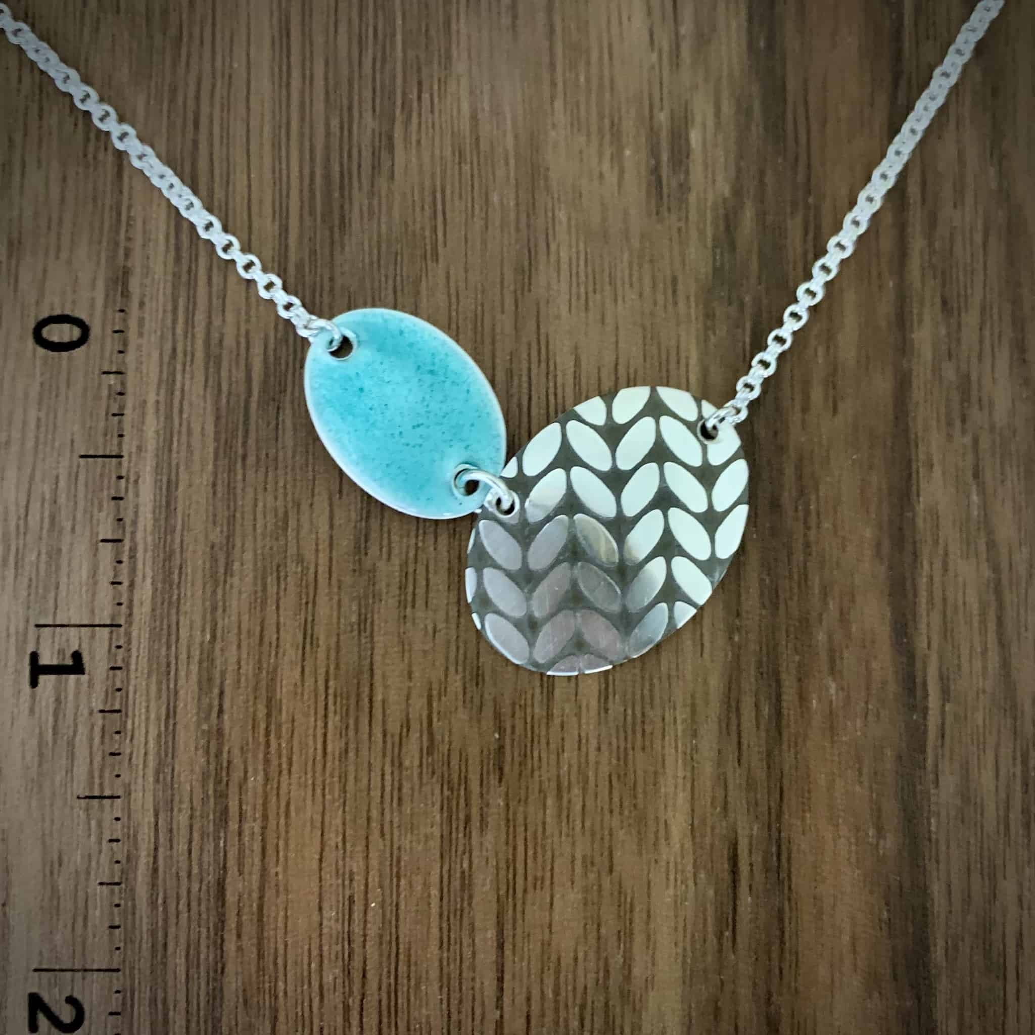A necklance with a silver stickinette stitch pattern and an aqua enamel oval.