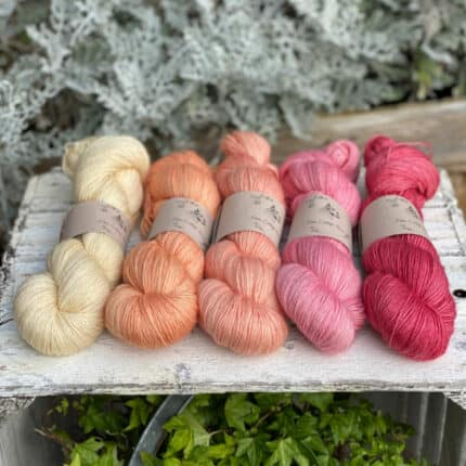 Skeins of yellow, peach and pink yarn in a row.