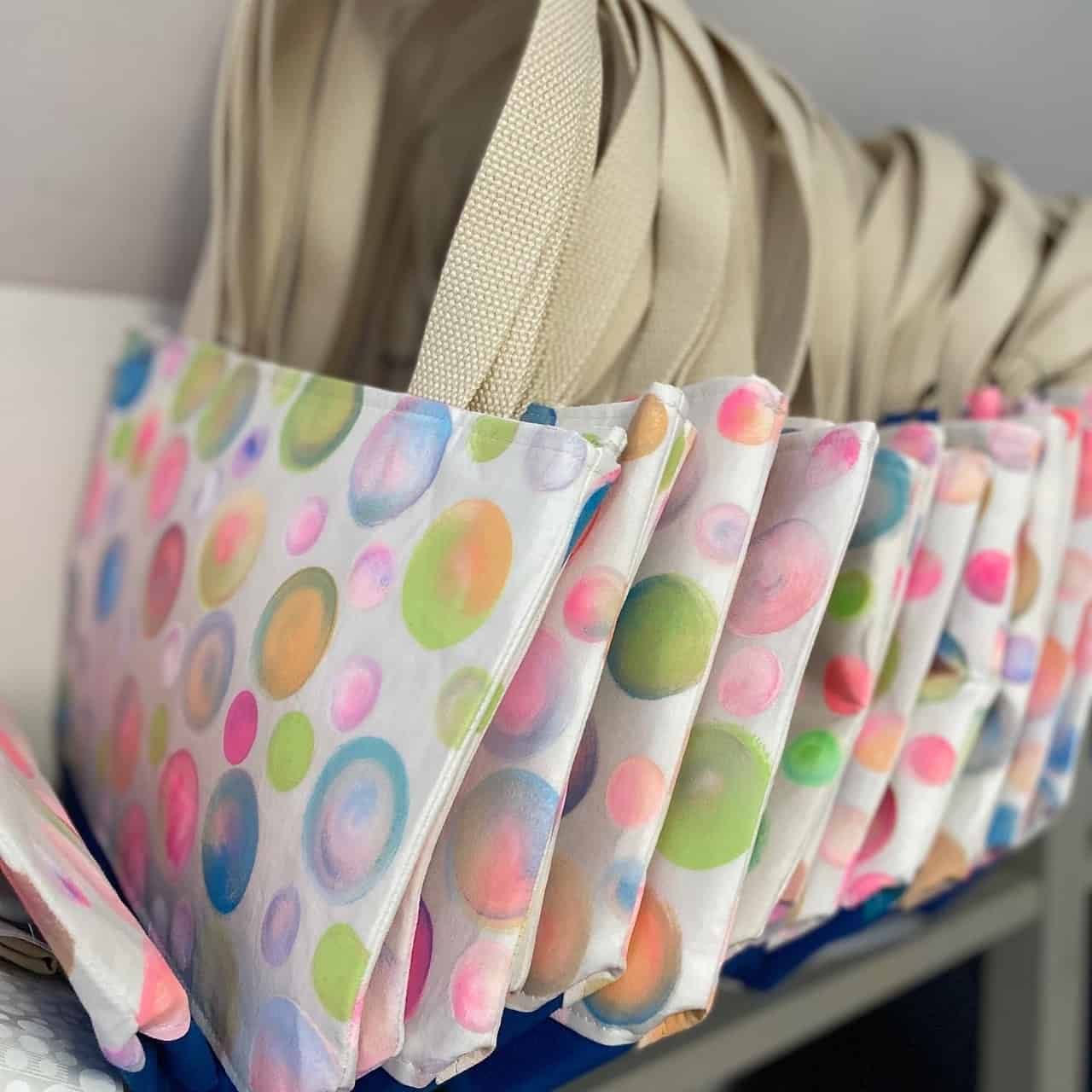 A row of tote bags with purple, green and pink dots.