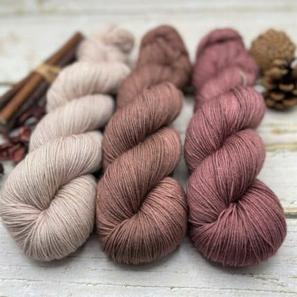 Skeins of cream, brown and mauve yarn surrounded by cinnamon sticks and pinecones.