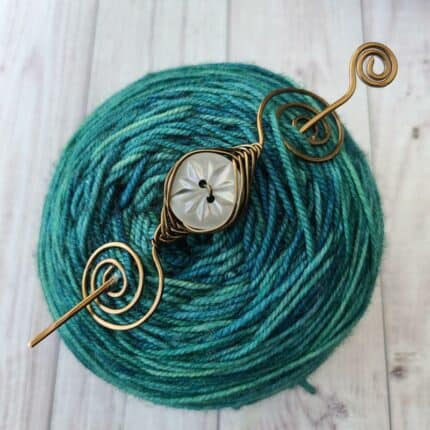 A spiral-edged pin with a mother of pearl button in the center sits atop a cake of green yarn.