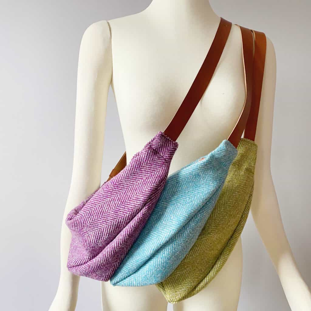 Purple, aqua and green tweed bags with brown leather straps sit across a mannequin.