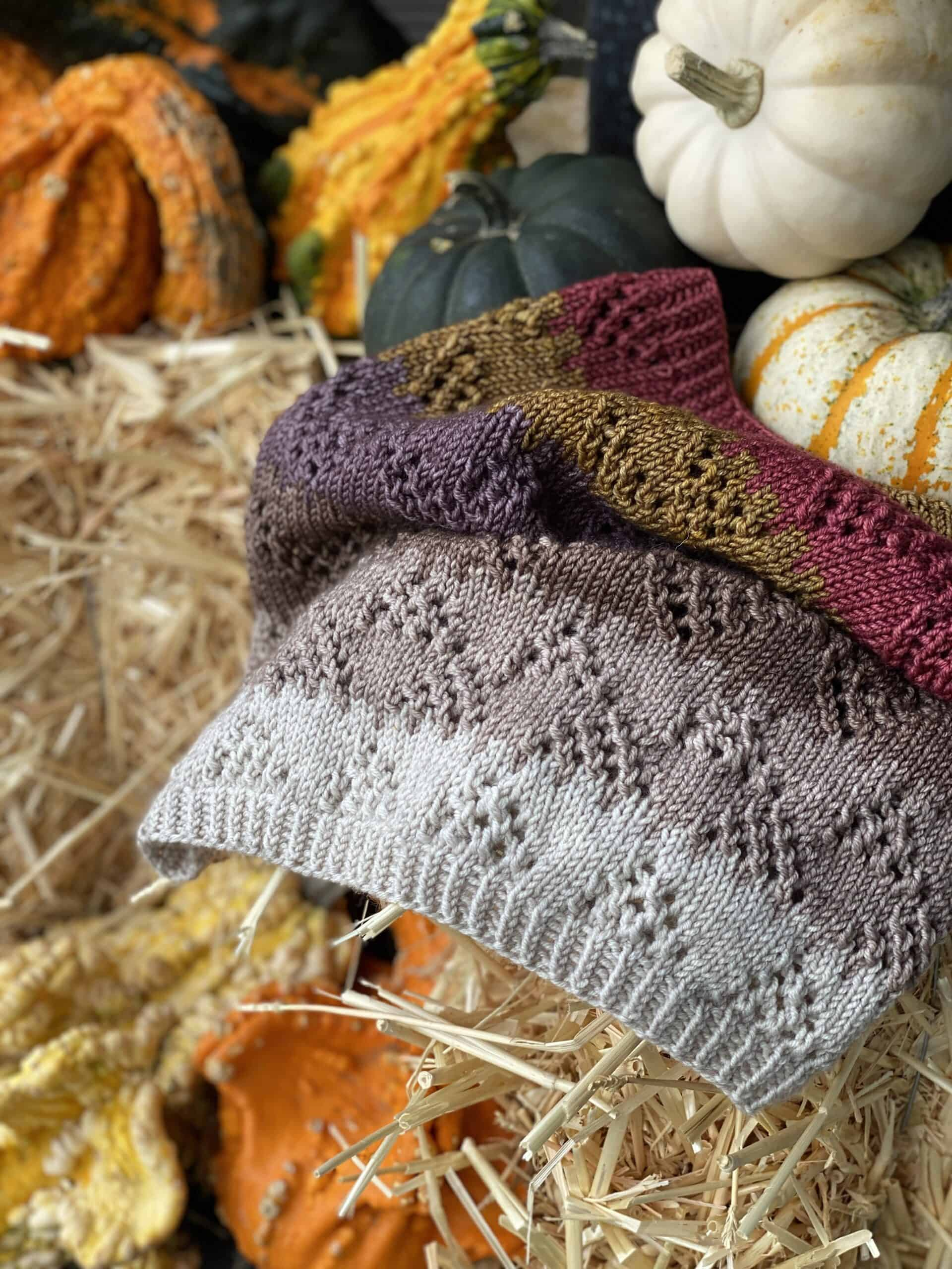A lacy cowl with gray, brown and red stripes with mini pumpkins.