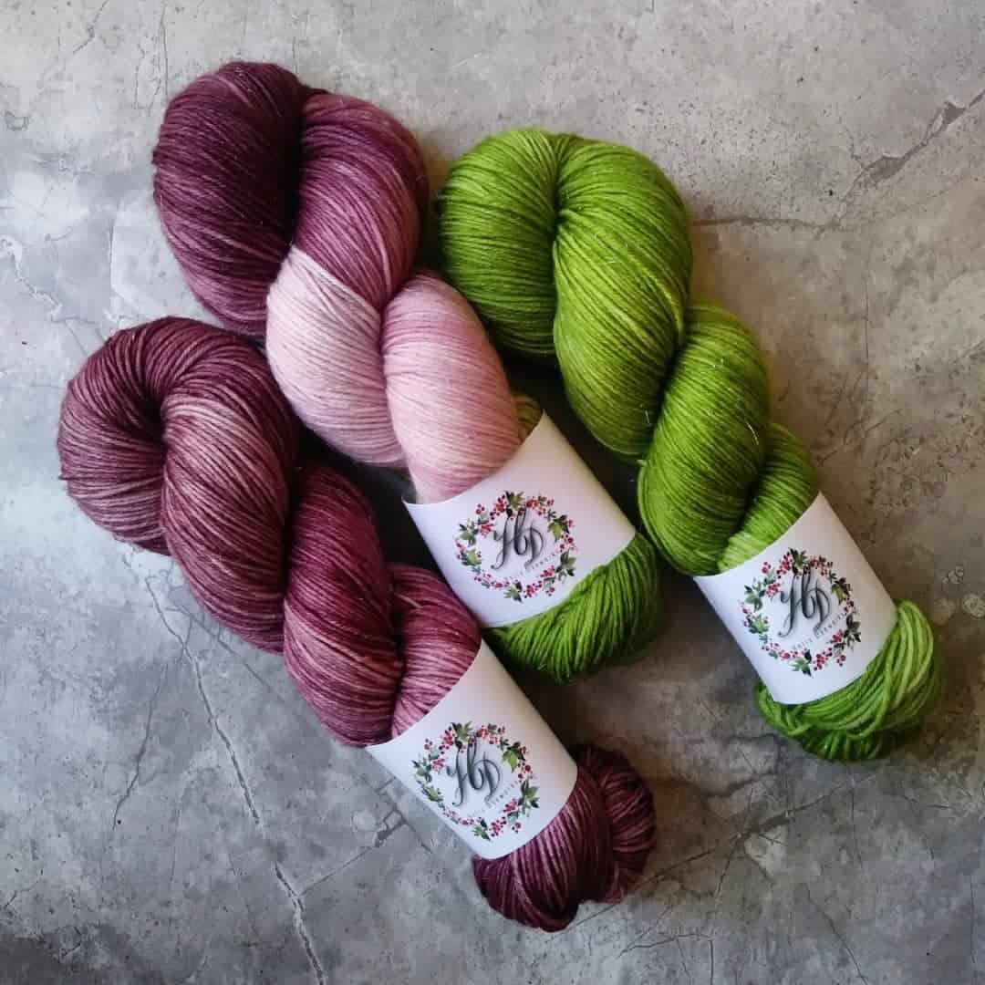 A trio of purple and green yarn.