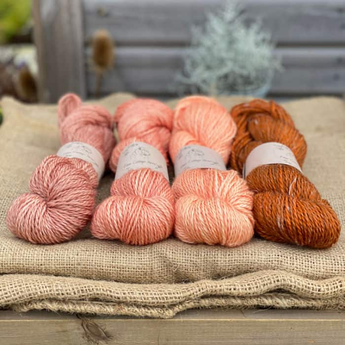 Skeins of pink and rust yarn.