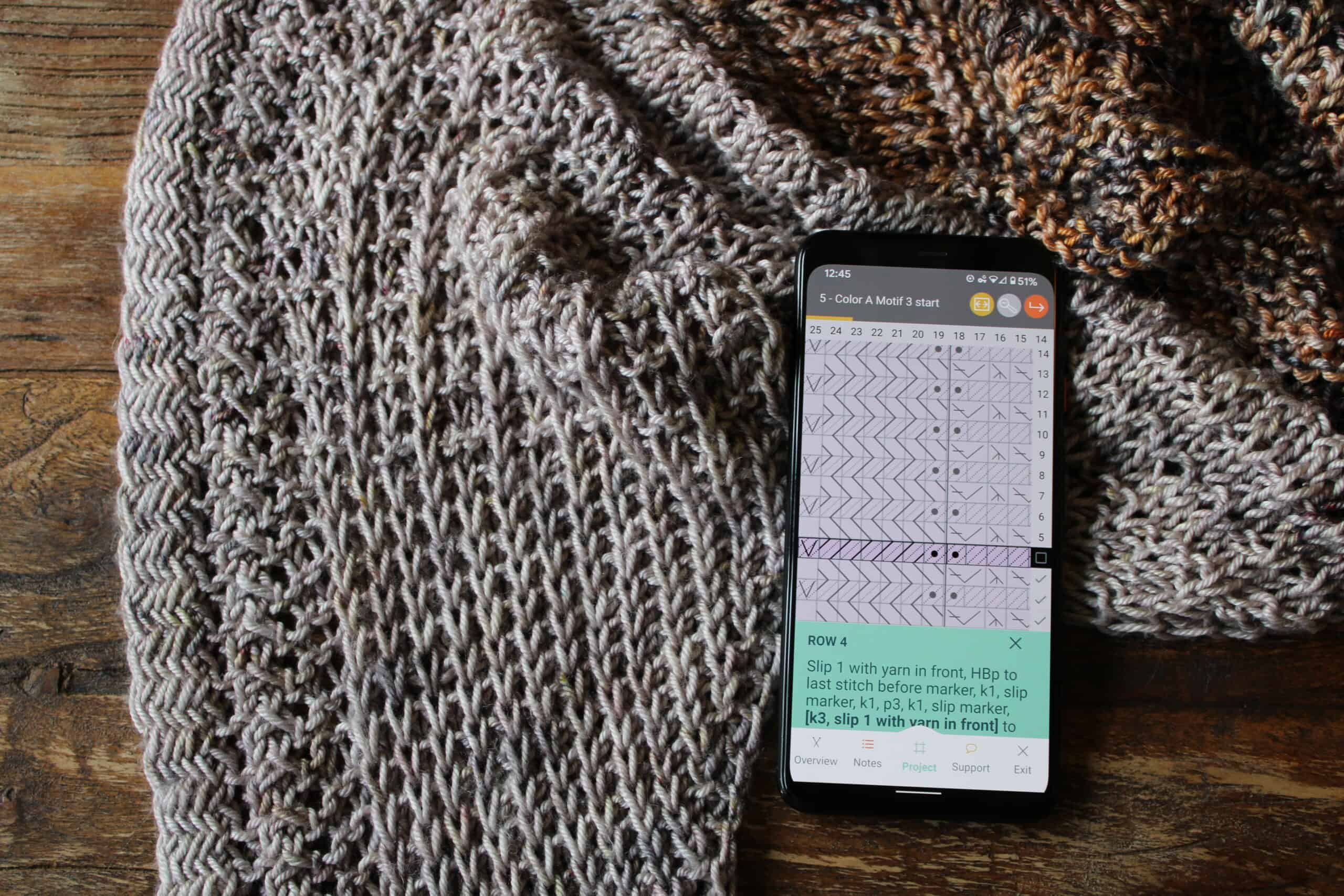 A smartphone next to gray knitting.