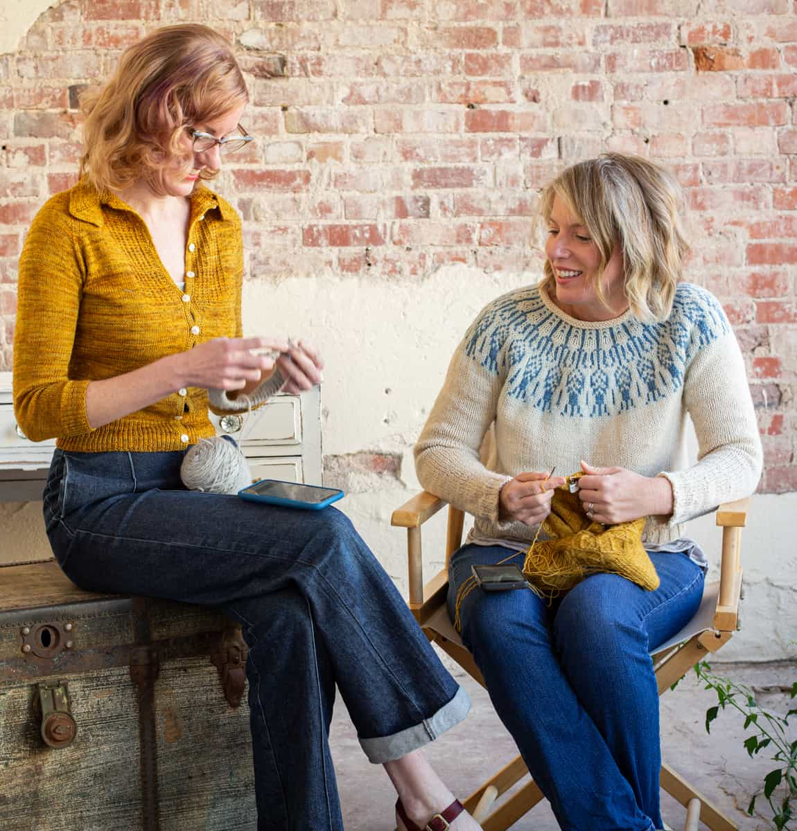 Two women knitting. They are wearing gold and blue colorwork sweaters.