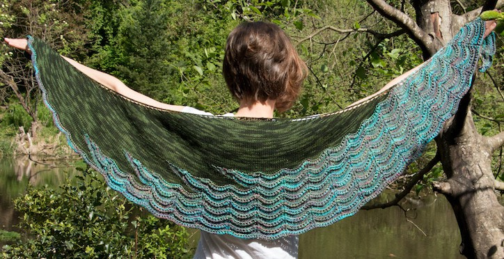 A green crescent shawl with a blue and gray edging of wavy lace.